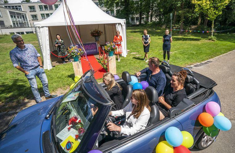 In Zeist reden leerlingen met hun familieleden door een drive-through diploma-uitreiking.  Beeld ANP