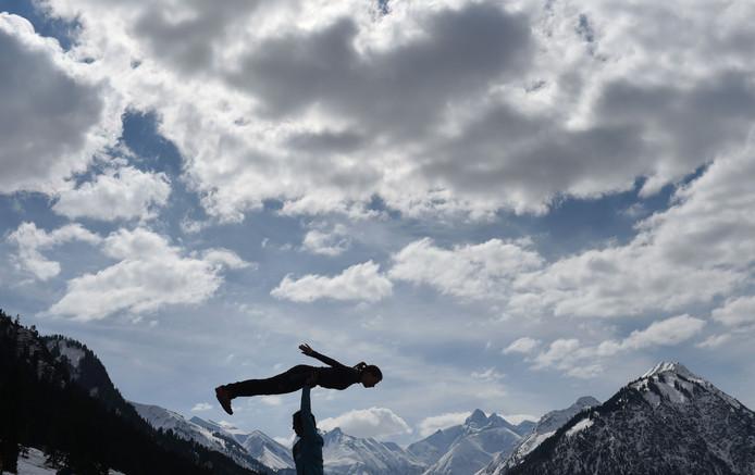 De Sloveense Ema Klinec doet met haar coach oefeningen, voorafgaand aan een schansspringwedstrijd in Oberstdorf in Duitsland. Foto Christof Stache
