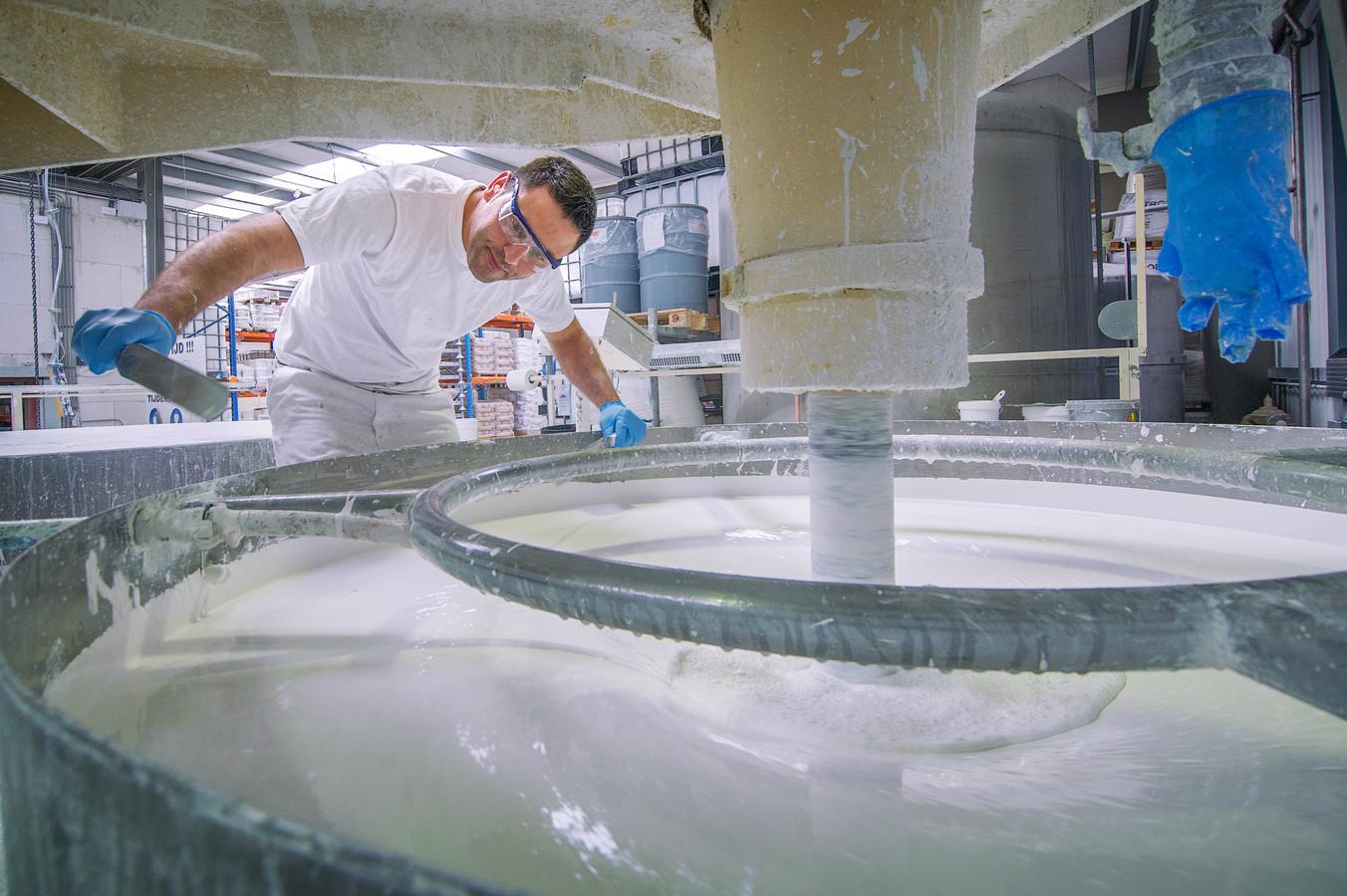 In grote bakken worden bij Global Paint Products de ingrediënten gemengd tot een dikke witte muurverf.
