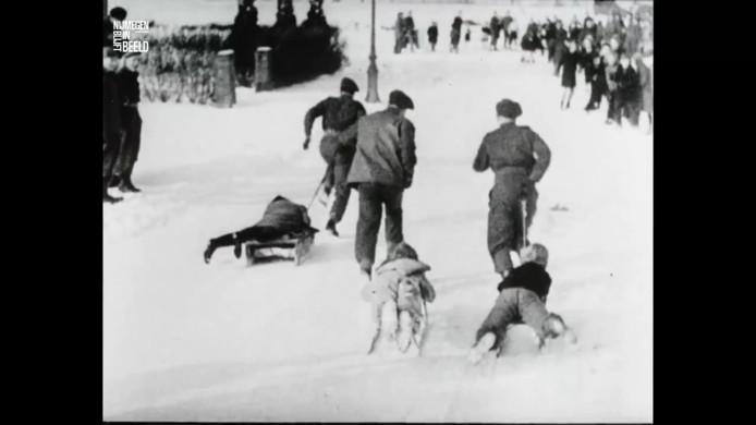 Canadese soldaten trekken kinderen uit Hatert voort op hun slee, tijdens een wedstrijd in de winter van 1944-1945.