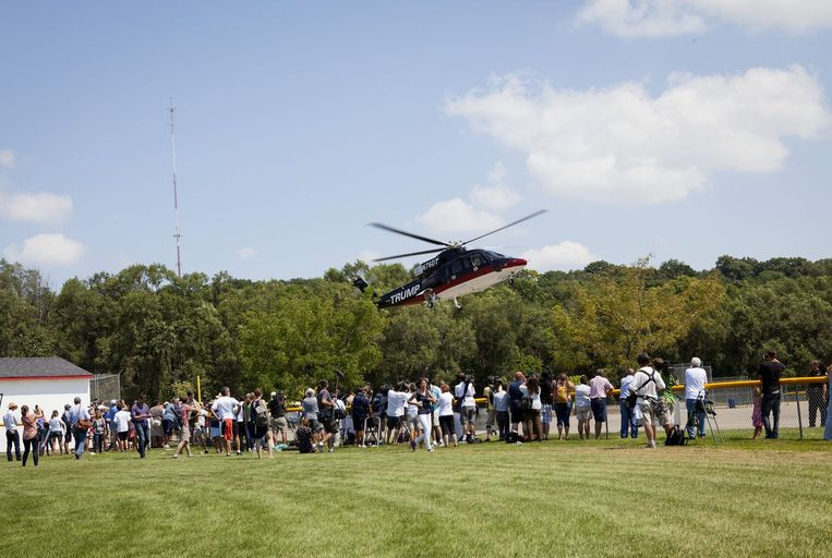 Aanhangers rennen naar de helikopter van Donald Trump.