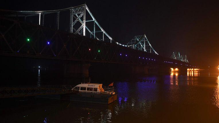Chinese patrouilleboot op de Yalu rivier op 3 september. De brug verbindt Dandong (China) en Sinuiju (Noord-Korea). Beeld afp