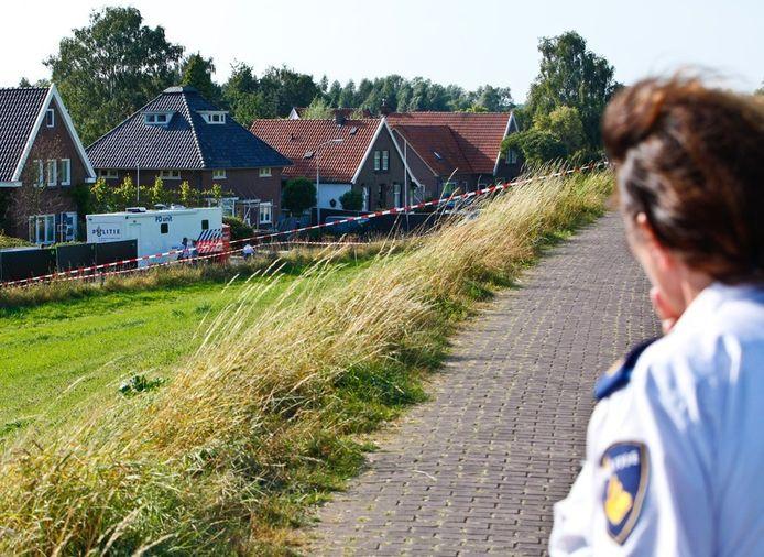 Een politieagente kijkt vanaf de dijk in het Gelderse Kekerdom naar de woning waar de drie lichamen en de wietkwekerij zondag werden aangetroffen.