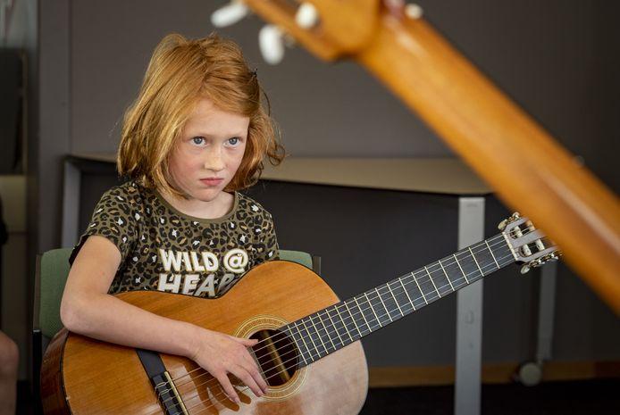 Mila Emsbroek (7) uit Borculo wil graag gitaar spelen en kijkt geconcentreerd naar muziekdocent Gerard Kroeze.