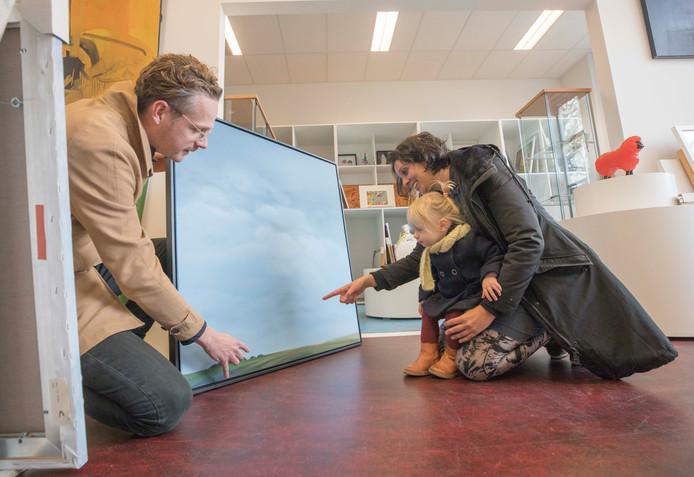 Eduard Walhout, Imke Elstak en dochtertje Jules Elstak komen een stuk uitkiezen bij de kunstuitleen in Goes.