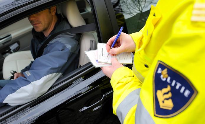 De politie schrijft een bekeuring uit. Vorig jaar zijn beduidend meer automobilisten staande gehouden.