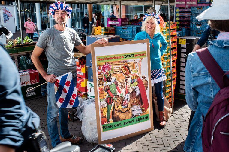 Mensen betogen bij de ingang van de rechtbank van Leeuwarden voor zwarte piet.  Beeld Simon Lenskens