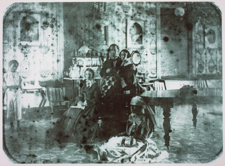 Paramaribo, ca. 1860. Portret van Guillaume Jacques Abraham Bosch Reitz (1825-1880) en zijn gezin, met twee slaven: rechts vooraan op de grond met een kind op schoot, en staand linksachter.  Beeld Nederlands Instituut voor Kunstgeschiedenis