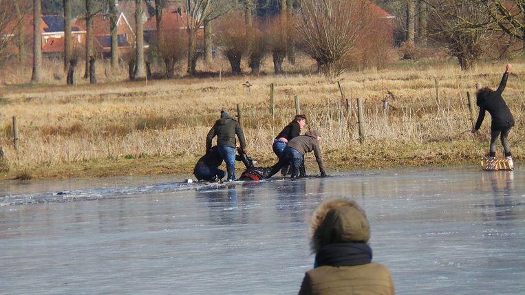 Omstanders hadden het niet makkelijk om de man uit het water te halen.
