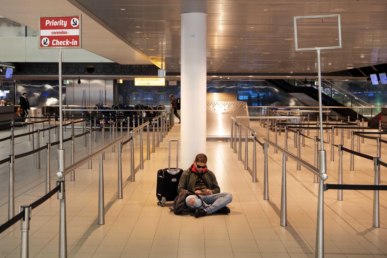 Een reiziger zit op de grond op luchthaven Schiphol.  Beeld EPA