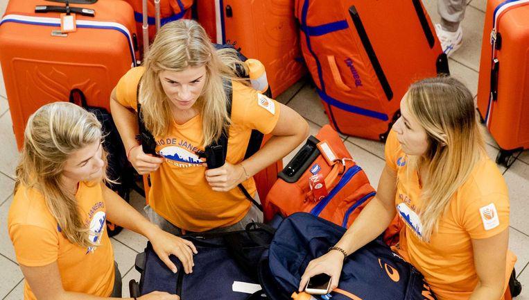 Drie leden van de vrouwenhandbalploeg in de vertrekhal van Schiphol. Beeld ANP