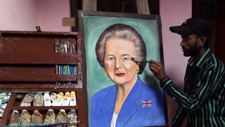 Een kunstenaar uit India maakt een schilderij van Margaret Thatcher als eerbetoon. Beeld epa