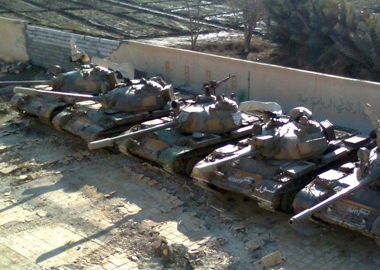 Syrische legertanks verstopt op een schoolterrein voor de komst van de VN in de stad Deir al-Zor. Beeld AFP PHOTO / HO / SHAAM NEWS NETWORK