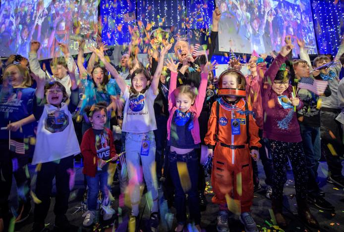 Schoolkinderen vieren het succes van New Horizons.