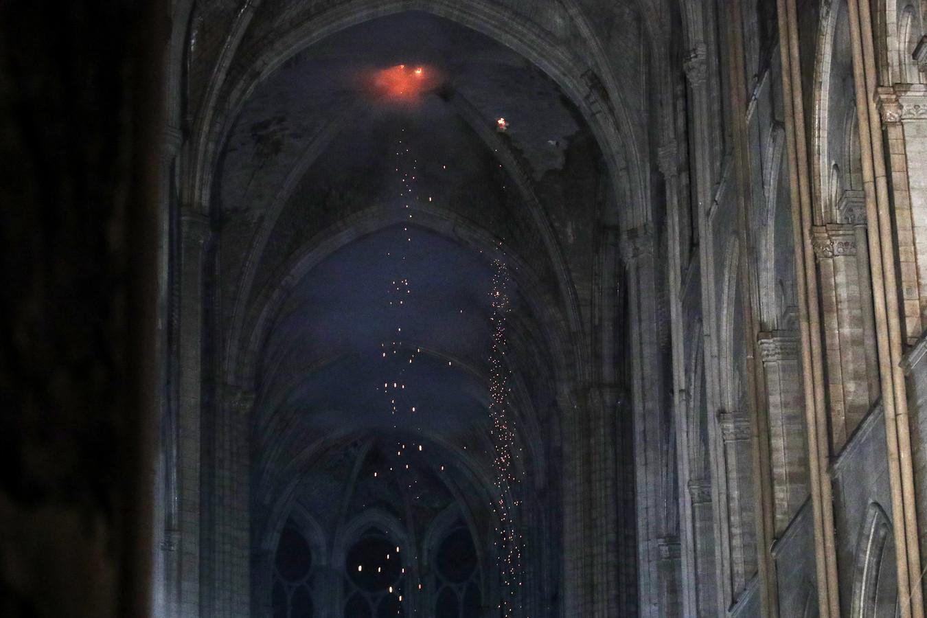 Vuur vreet zich een weg naar de binnenkant van de kerk. Het regent vonken.