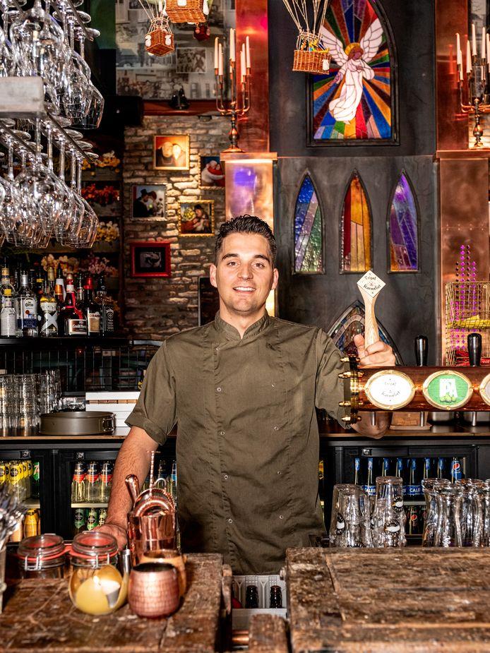 Luc Dielissen aan de bar met op de achtergrond de koperen replica van Onze Lieve Vrouwetoren.
