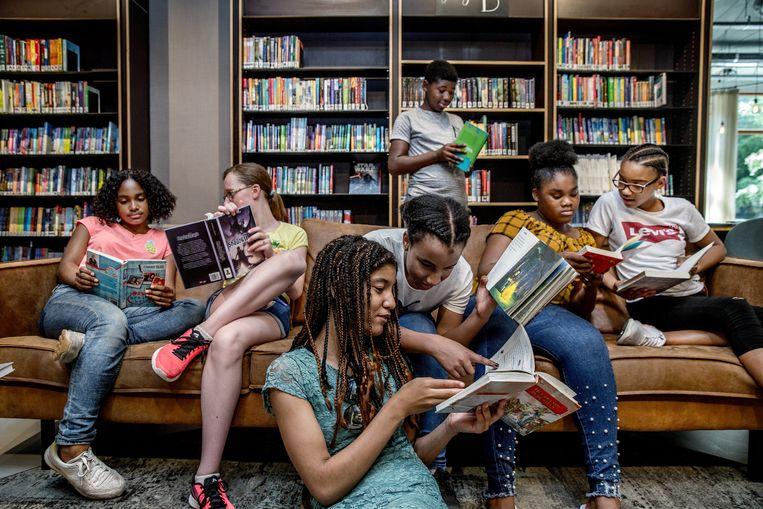 In de openbare bibliotheek in het Amsterdamse stadsdeel Zuidoost wordt het rapport over de staat van het lezen onder Nederlandse jongeren gepresenteerd. Edith Hooge (onderwijsraad) en Marijke van Hees van de raad voor Cultuur zijn aanwezig. Pubers op een bank lezen boeken. Beeld Jean-Pierre Jans