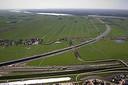 Het consortium verkocht bouwgrond zoals hier voor bypassdorp Reeve aan de gemeente, om er zelf weer te kunnen bouwen. Op de voorgrond de N50, en midden op de foto de richting Flevoland afbuigende Hanzelijn.