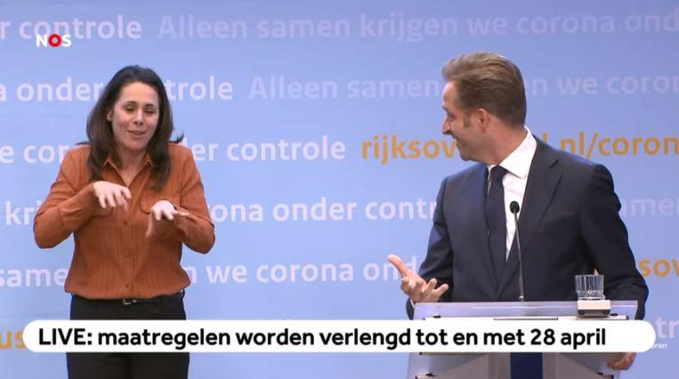 Minister Hugo de Jonge en gebarentolk Irma Sluis tijdens de persconferentie van dinsdag 31 maart. Beeld NOS