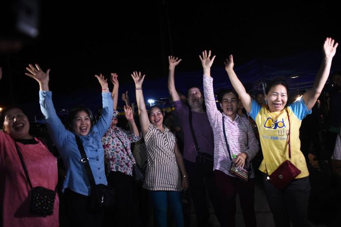 Vrijwillige hulpverleners juichen om het goede nieuws dat de voetballers allemaal gered zijn.
