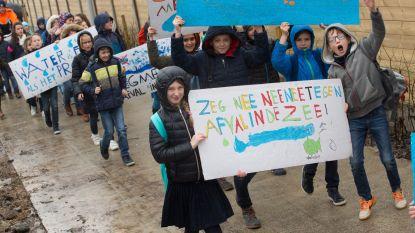 Schoolgaande jeugd op straat voor proper water
