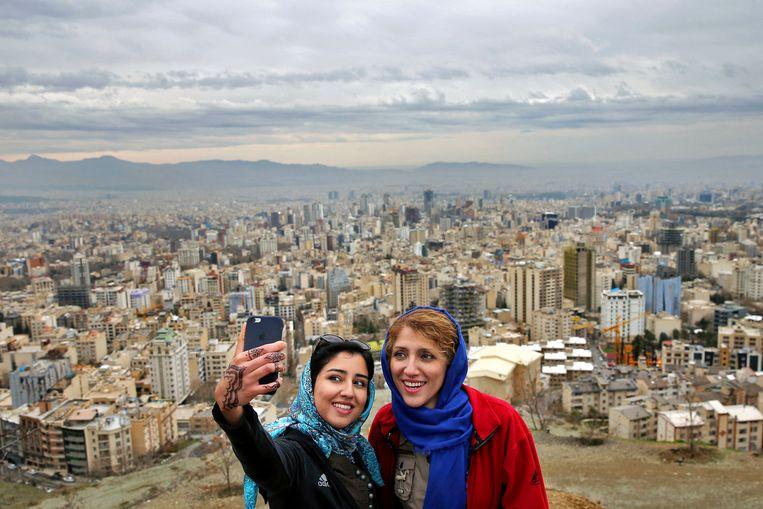 Twee vrouwen nemen een selfie om het Sizdeh Beder festival te bekijken. Een jaarlijkse picnic dag op 13 april in het Iranese nieuw jaar. Beeld AP