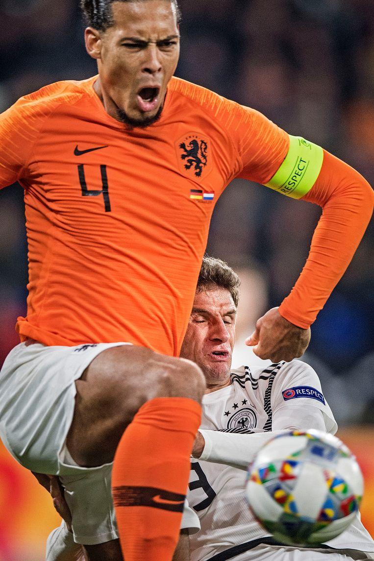 Virgil van Dijk (Nederland) blaast Thomas Muller Duitsland) omver, 19 november 2018. Beeld null