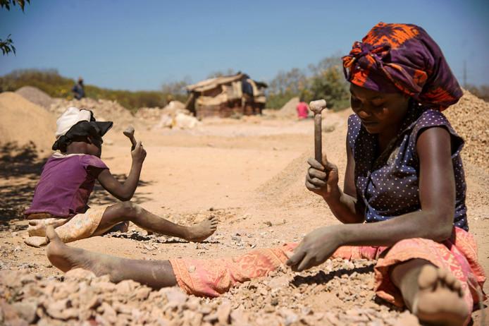 Een vrouw en een kind slaan stenen stuk bij een mijn in Congo om kobalt te winnen. Het zeldzame metaal is cruciaal voor moderne batterijen in auto's en computers.