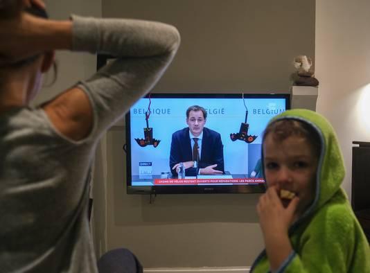 Een Belgisch gezin luistert naar premier Alexander De Croo, die een verstrengde lockdown aankondigt.