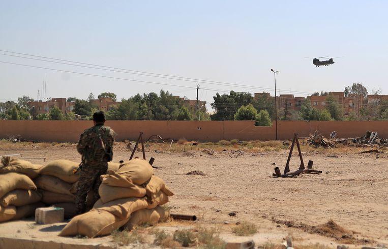 De coalitie onder leiding van de Verenigde Staten zegt vandaag dat de laatste fase van de militaire operatie tegen terreurbeweging IS is ingegaan in het oosten van Syrië. Een lid van de SDF kijkt hoe een Amerikaanse Chinook-helikopter wegvliegt nabij Shadadi.