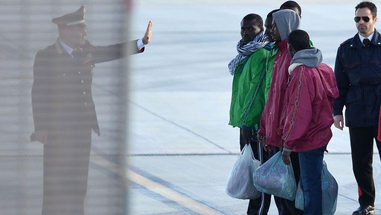 Carabinieri geeft instructie aan migranten op het vliegveld van Lampedusa. Beeld anp