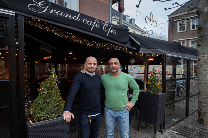 Yilmaz (r) en Appie Iyi serveren op eerste kerstdag een gratis kerstdiner voor minima.