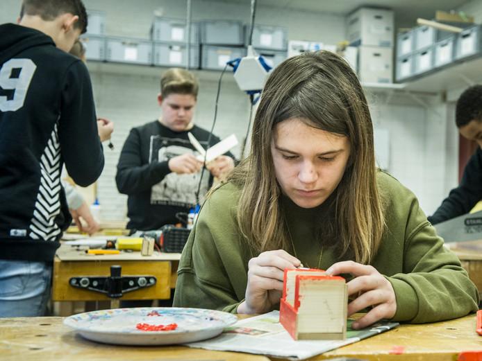 Nienke werkt tijdens de techniekles op De Keyzer geconcentreerd aan een pennenbakje dat ze zelf heeft gemaakt.