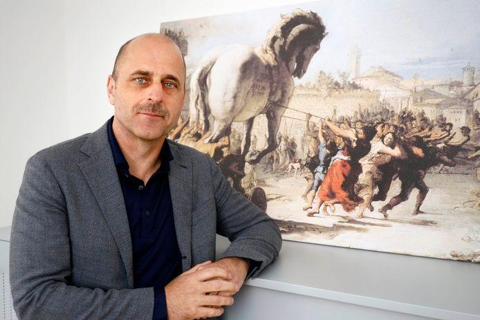 Ypke van Oosterhout op zijn kantoor in Nijmegen bij een schilderij met het Paard van Troje, een verwijzing naar hoe het medicijn dat hij ontwikkelt te werk gaat.
