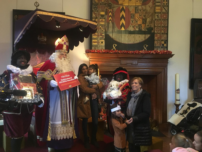 De familie Swinkels krijgt uit handen van Sinterklaas de cadeaubon uitgereikt.