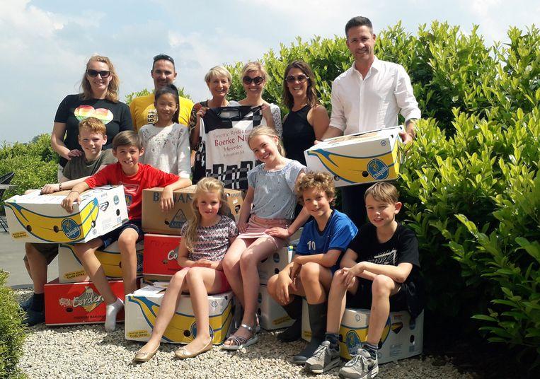 Sofie Vervloet, Nico Luyten, Kathleen Nys, Daniella Aerts en de kinderen helpen Kristof en Kelly bij de verhuis van de bananendozen vol kledij voor Make Gambia Smile.