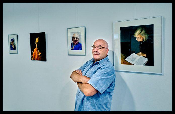 Kunstenaar Ries Fiere poseert bij een deel van de expositie met lokale, 's-Gravendeelse portretten én zijn zelfportret.