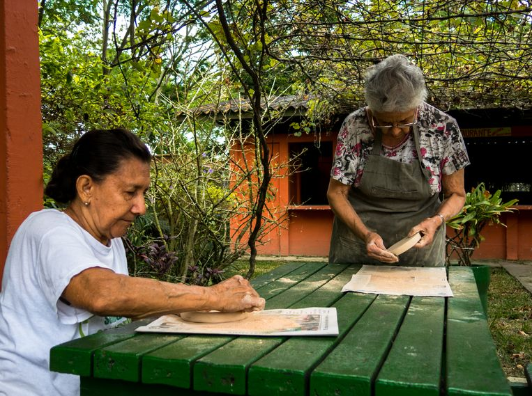 Eyda Delgado (links) werkt samen met keramiek-docente Amparo Gonzalez aan een bestelling borden van klei.  Beeld Ynske Boersma