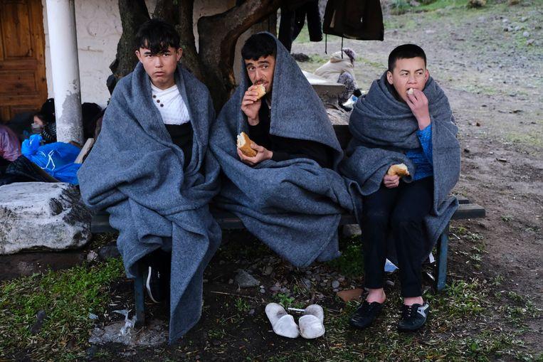 Drie migranten, die donderdag vanuit Turkije in Griekenland zijn aangekomen, proberen warm te blijven. Beeld AP