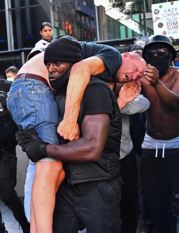 Een zwarte demonstrant brengt, geflankeerd door de politie, een gewonde tegen-demonstrant in veiligheid in de buurt van het Waterloo Station in Londen.