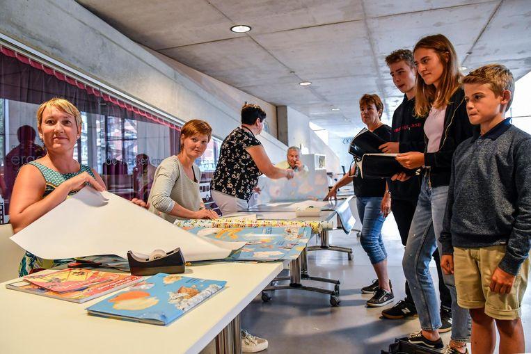 Enkele scholieren laten hun boeken kaften.