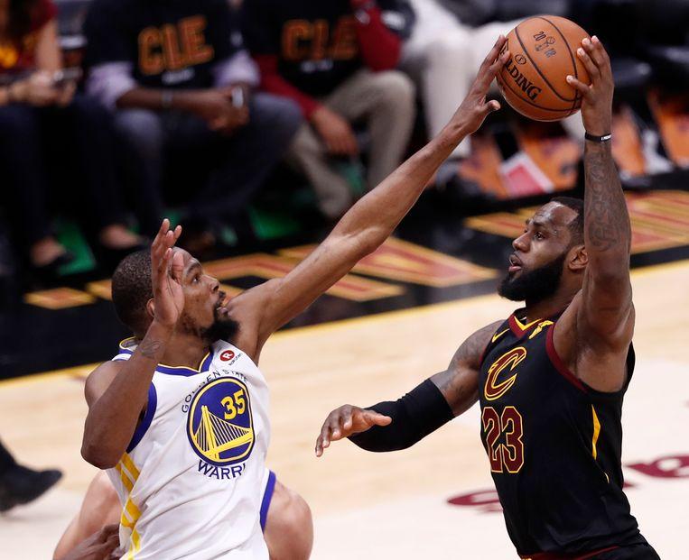 Kevin Durant (links) blokkeert een schot van LeBron James tijdens de derde wedstrijd van de NBA-finale Beeld EPA