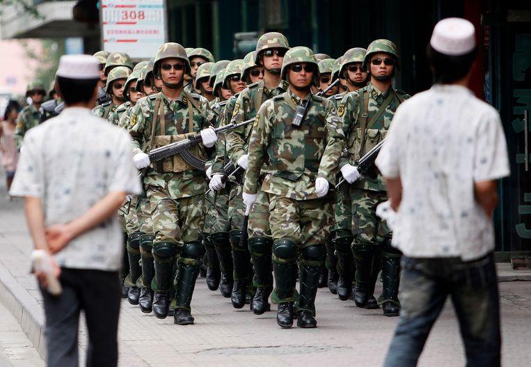 Chinese ordetroepen in Urumqi. Tien jaar geleden kwam het in deze stad in Xinjiang tot flinke rellen. Sindsdien probeert Beijing de Oeigoeren en andere minderheden onder controle te krijgen. Beeld AP