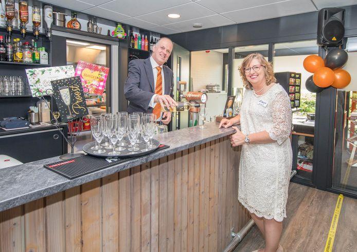 Beheerder Ronny Menheere schenkt achter de nieuwe bar een wijntje in voor bestuurslid Ellemijn van Waveren.