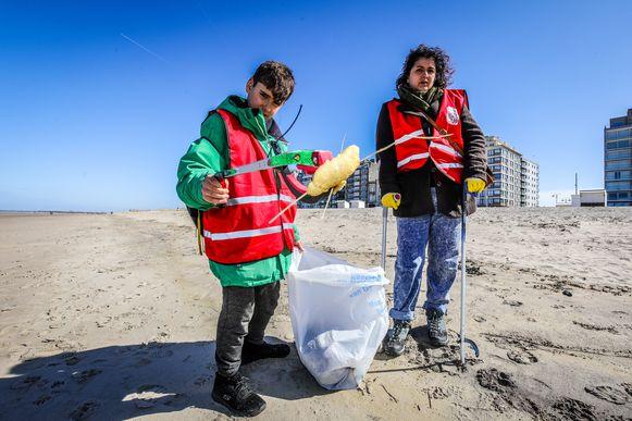 Moeder en zoon ruimen samen het strand op.