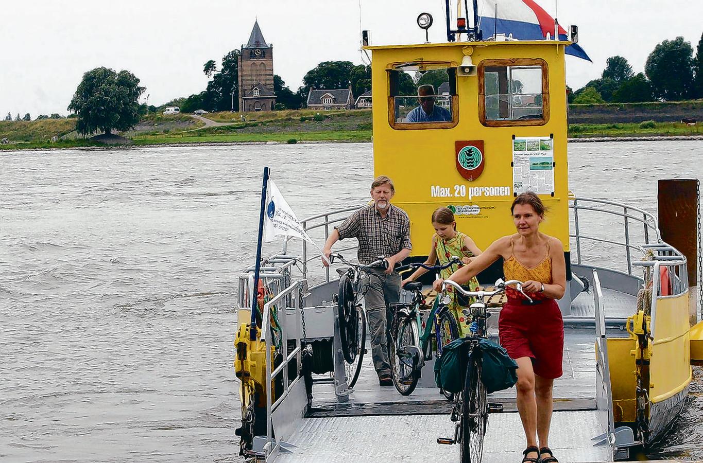 Nog nooit was het pontje tussen Heerewaarden en Varik zo in trek bij fietsers en voetgangers als dit seizoen. Op de achtergrond de Dikke Toren van Varik.