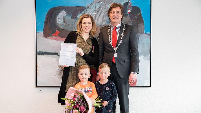 Esther Holierhoek met haar kinderen, oorkonde en burgemeester Verhulst.