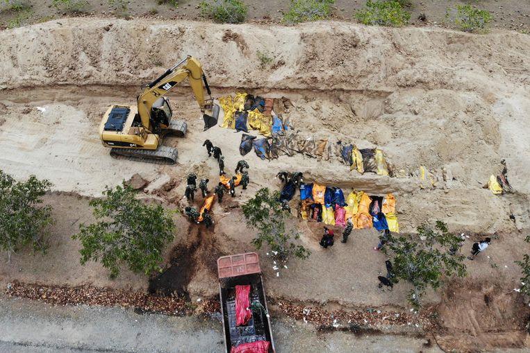 Indonesische soldaten bergen de lichamen van slachtoffers bij een massagraf in Poboya. Beeld AFP