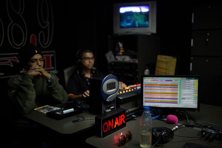 De producers van de radioshow van Isnardo Bravo luisteren naar de zender.  Beeld Andrea Hernandez