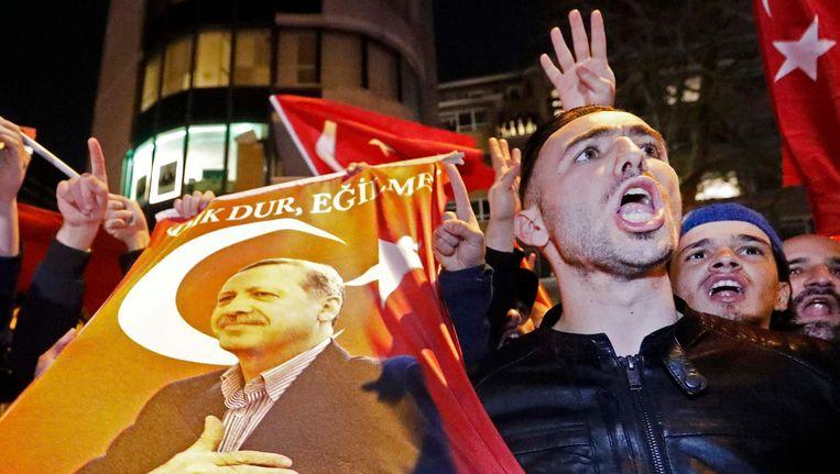 Erdogan-aanhangers demonstreren bij het Turkse consulaat in Rotterdam omdat de komst van minister Kaya wordt tegengehouden. Beeld reuters